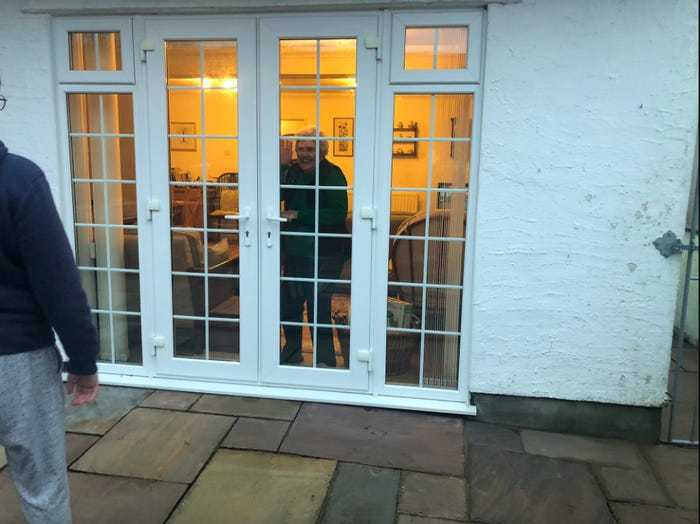 Social distancing photo gallery - an elderly speaking through a closed window
