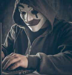 Coronavirus and Phishing - hacker with clown mask and hoodie in front of laptop