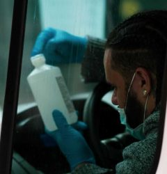 Coronavirus and Taxis - taxi driver with mask in the car looking at bottle of hand sanitiser