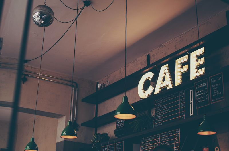instagram photo ideas for cafes in 2020 - ceiling of a dark cafe with the sign cafe in white
