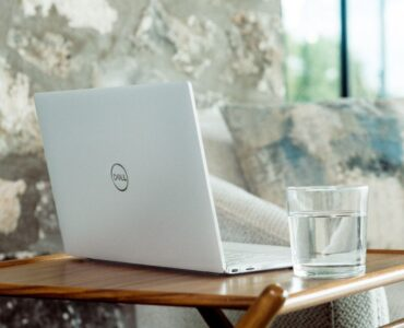 digital marketing things - laptop and glass of water on little wooden table