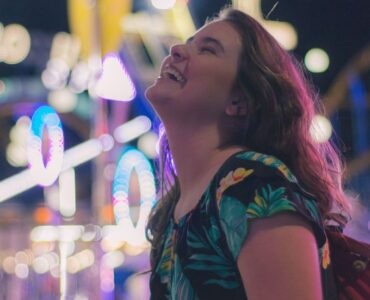 being authentic - woman laughing at theme park at night
