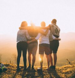 speak like a person - group of four people hugging at sunrise
