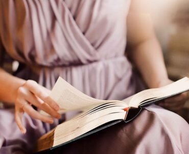stories vs case studies - woman in pink dress reading a book