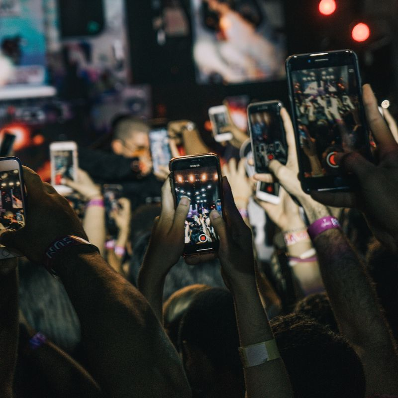 what is the solomo mindset - group of arms at live concert holding mobile phones in the air