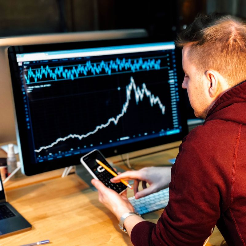 red haired man looking at data chart on dark monitor holding a mobile phone