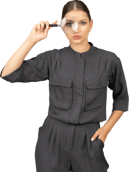 front view of a young woman in a jumpsuit holding a magnifying glass removebg preview 1